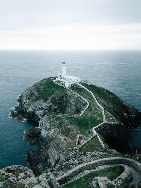 Снимок маяка на скале в rspb south stack cliff, англси, уэльс Бесплатные Фотографии
