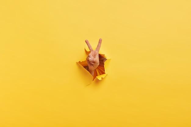 Выстрел до неузнаваемости человека демонстрирует знак победы через рваную дыру в желтой бумаге Бесплатные Фотографии
