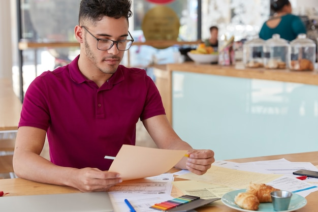 형태가 이루어지지 않은 남자의 샷은 서류를 검사하고, 스티커를 사용하고, 캐주얼 티셔츠와 안경을 착용합니다. 창의적인 남성 블로거는 문서 작업을하고 열심히 일하며 새로운 전략을 개발합니다. 무료 사진