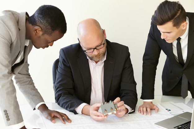 건설 디자인 국에서 작업 과정의 총. 새로운 관점 프로젝트를 검토하는 사무실 옷에 세 남자. 테이블에 앉아있는 메인 디자인 엔지니어, 그의 동료들은 그의 옆에 서 있습니다. 무료 사진