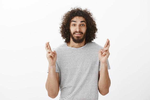 Снимок встревоженного бородатого восточного мужчины-модели с афро-прической в полосатой футболке, поднимающего скрещенные пальцы и надеющегося, загадывающего желание и умоляющего исполнить его Бесплатные Фотографии