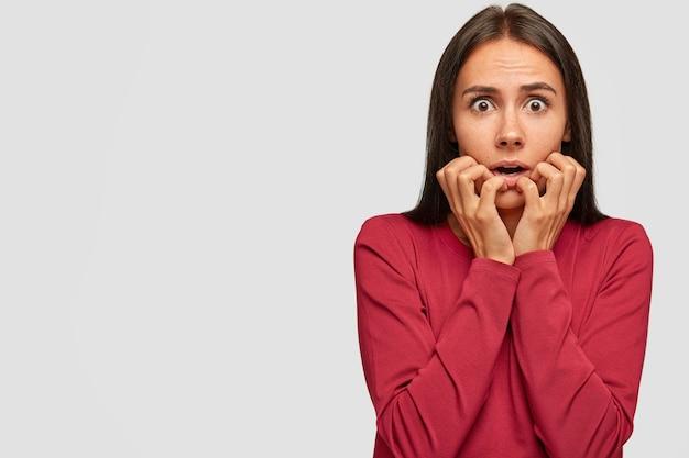 心配している怖いブルネットの若い女性のショットは神経質に指の爪を噛みます 無料写真
