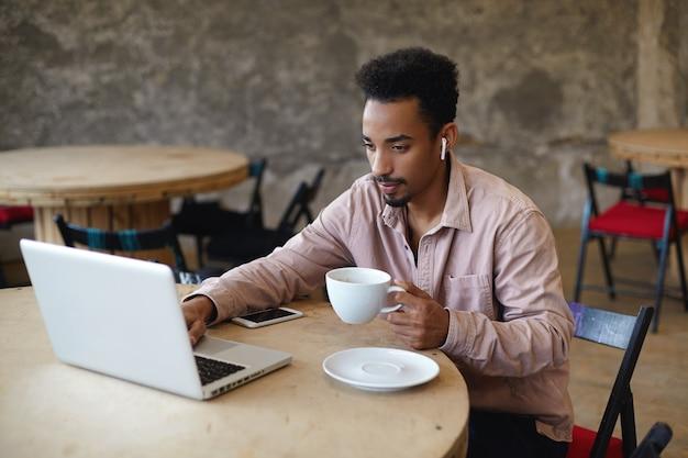 젊은 어두운 피부의 남성 프리랜서의 총은 현대 노트북과 스마트 폰이있는 커피 하우스에서 원격으로 작업하는 베이지 색 셔츠를 입고 집중된 얼굴로 화면을보고 커피 한잔 들고 무료 사진
