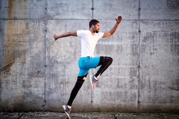젊은 스포티 한 선수의 총 콘크리트 벽 배경 점프 무료 사진