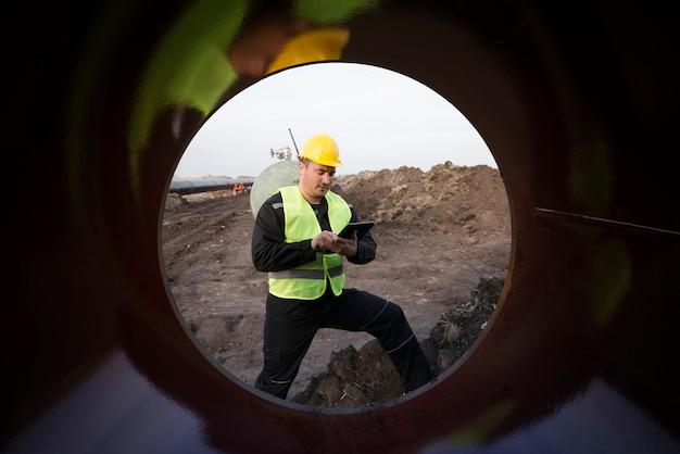 Colpo di un operaio del giacimento di petrolio che controlla la qualità dei tubi del gas al cantiere Foto Gratuite