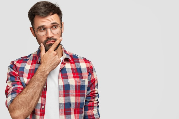 Shot of pleasant looking bearded male holds chin, looks pensively aside, holds chin, focused aside, stands against white wall Free Photo