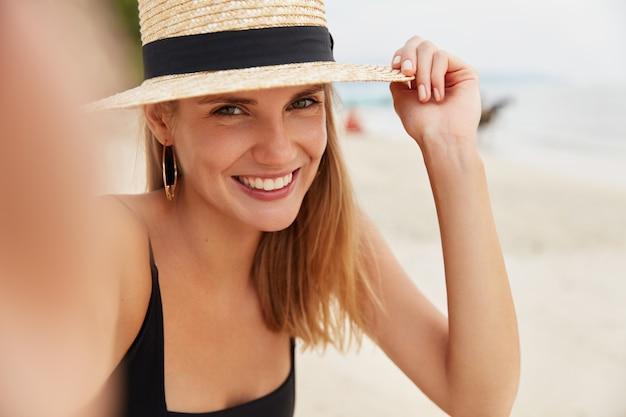 Colpo di donna sorridente dall'aspetto piacevole con cappello di paglia, ha un sorriso splendente, posa per selfie sullo sfondo dell'oceano, essendo di alto spirito mentre trascorre le vacanze estive in un luogo paradisiaco con l'amante Foto Gratuite