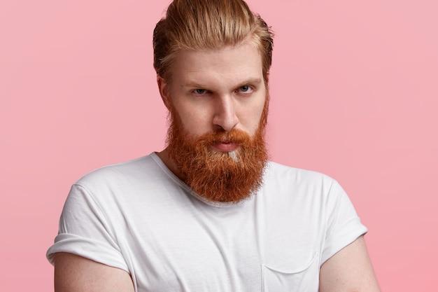 Colpo di serio giovane dai capelli rossi con una lunga barba rossa, espressione riservata, guarda con sicurezza Foto Gratuite
