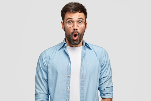 Shot of terrified unshaven man stares with eyes full of disbelief, being surprised by curious revelation, wears blue shirt, isolated over white wall. people, reaction, facial expressions Free Photo