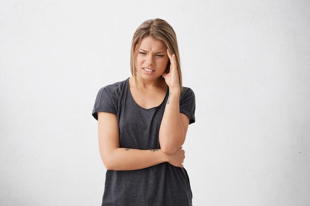 Выстрел измученной измученной женщины с печальным и изможденным взглядом, хмурым лицом, держащей руку на виске, собирающейся плакать, имея много проблем, не зная, как их решить. люди, стресс и проблемы Бесплатные Фотографии