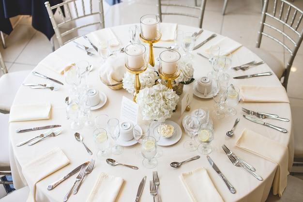 Colpo di mazzi di fiori bianchi e candele pilastro in candelabri d'oro su un tavolo di nozze Foto Gratuite