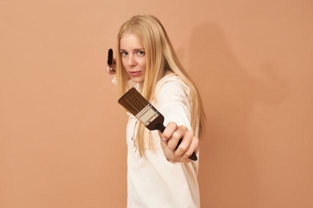 Colpo di giovane donna imbianchino in uniforme in posa isolato con due pennelli nelle sue mani Foto Gratuite