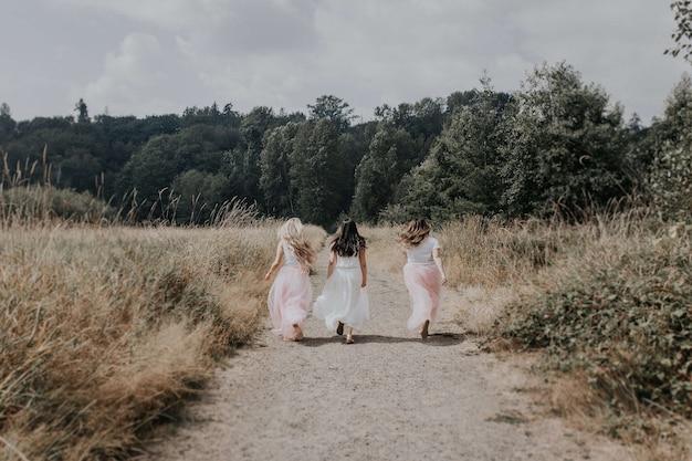 Dietro il colpo di giovani ragazze con bei vestiti che corrono nel campo Foto Gratuite