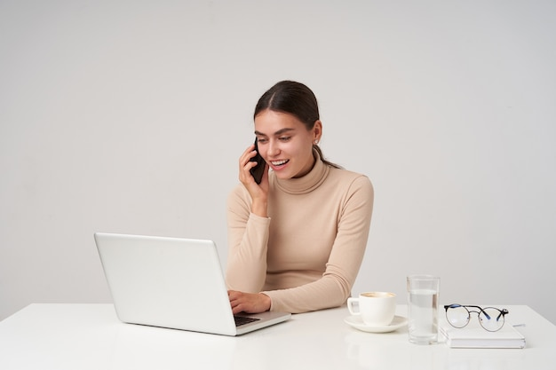 Shot of young pretty positive dark haired lady with natural makeup smiling cheerfully while making call and looking at screen while typing text on keyboard, isolated over white wall Free Photo