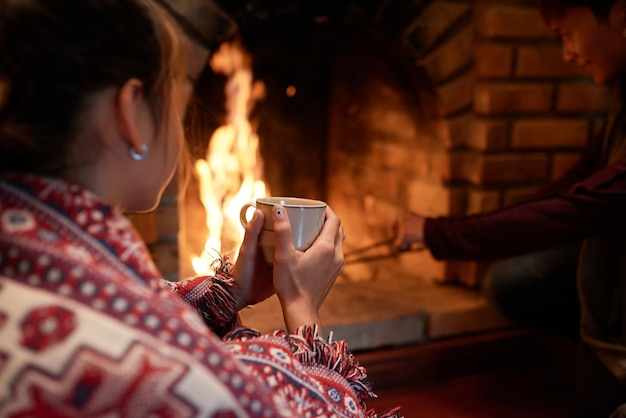 Over the shoulder shot of woman warming her hands on the mug of hot tea sitting at the fireplace, her boyfriend dealing with charcoal Free Photo