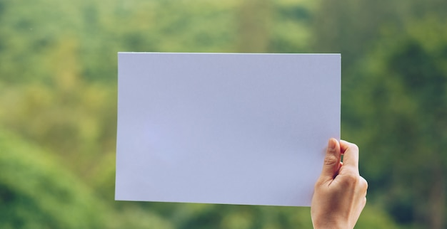 Show business paper in hand on nature background Premium Photo