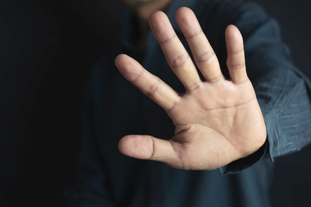 Show hand with stop gesture on black background Premium Photo