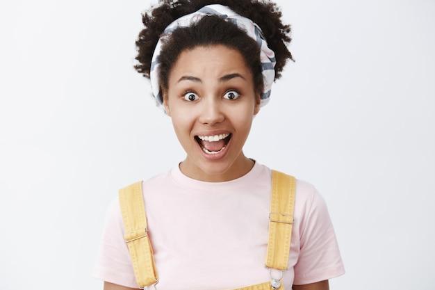 Mostrami il vero colore delle emozioni. ritratto di bella ragazza afroamericana eccitata, impressionata e sorpresa in fascia e tuta gialla, sorridente con la mascella abbassata, entusiasta sul muro grigio Foto Gratuite