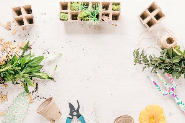 Завод; горшок с торфом; грабли; строка; showel; цветок; торфяной поднос и секатор на деревянном фоне Бесплатные Фотографии
