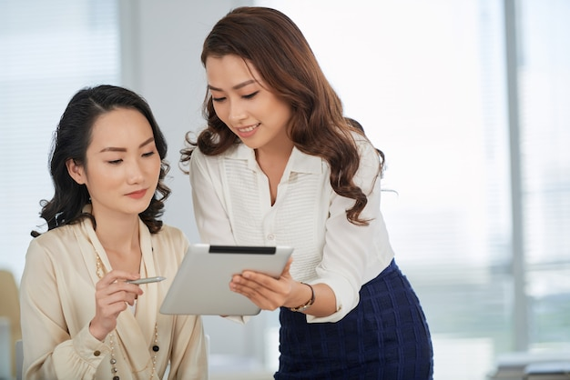 Showing business document to colleague Free Photo