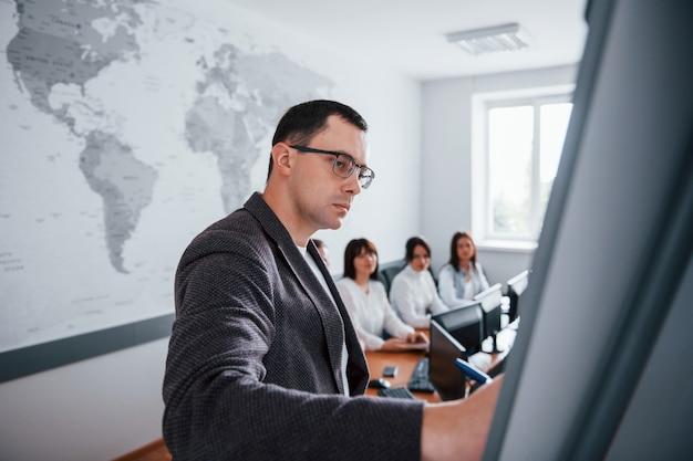 Visualizzazione di esempio sulla lavagna. gruppo di persone alla conferenza di lavoro in aula moderna durante il giorno Foto Gratuite