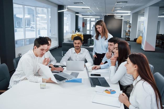 Показаны хорошие результаты. группа молодых фрилансеров в офисе разговаривают и улыбаются Бесплатные Фотографии