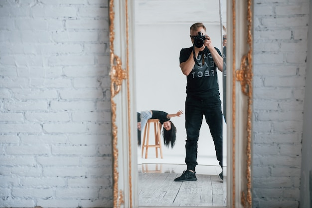 Sto mostrando ciao. uomo con la macchina fotografica che cattura un colpo nello specchio vintage. la ragazza si sta divertendo dietro Foto Gratuite