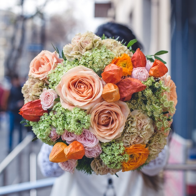 Showing a mixed flower bouquet in the street. Free Photo