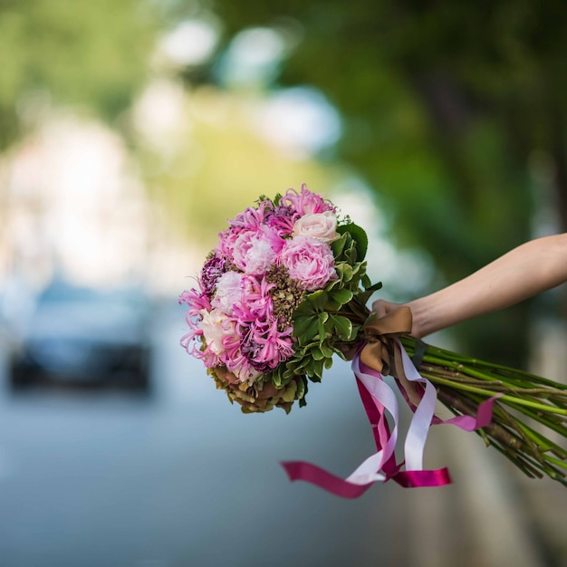 Showing a purple bouquet of roses and floss flowers in the street view Free Photo