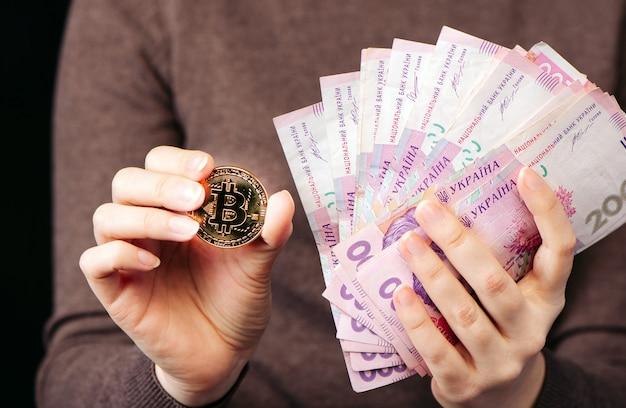 Показывает золотую монету биткойн - символ криптовалюты, новые виртуальные деньги и стопку денег украинской гривны, выборочный фокус, тонированный. Premium Фотографии