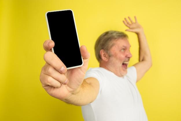電話の空白の画面を上向きに表示します。黄色のスタジオの背景に白人男性の肖像画。白いシャツの美しい男性モデル。 無料写真