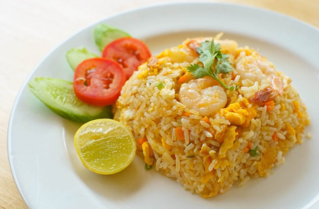 Shrimp fried rice with tomatoes, cucumbers and lemon . Premium Photo