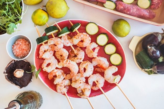 Shrimp kebabs served with vegetables and fruits Free Photo