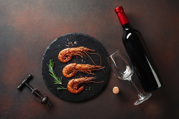 Shrimp with a bottle of wine. top view. free space for your text. on the old background Premium Photo