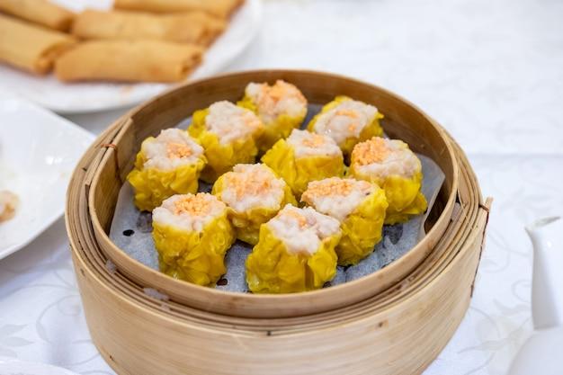 Shrimp yellow dumplings. dim sum set. in bamboo tray on table Premium Photo