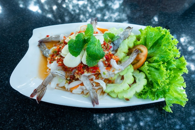 野菜と緑のスパイシーソースタイ料理の白い皿に魚醤で冷やしたエビ Premium写真