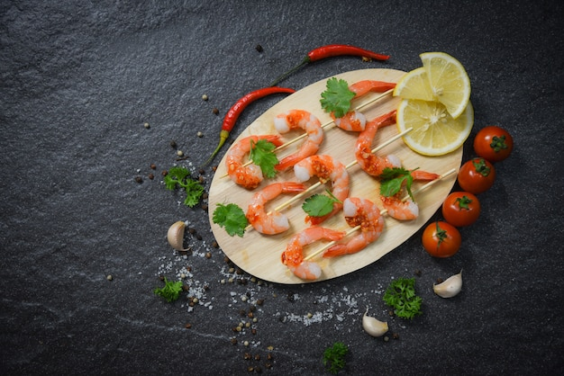 Shrimps prawns skewers seafood cooked with sauce herbs and spices on wood Premium Photo