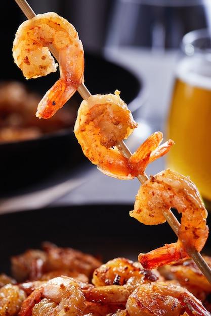 串に刺したエビ。黒いプレートとビールのグラスにニンニクとレモンをフライパンで揚げたエビ Premium写真