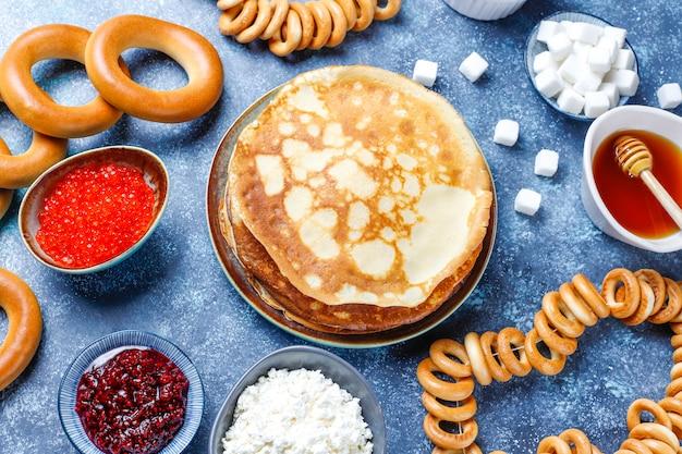 Масленица масленица фестиваль еды. русский блины блины с малиновым вареньем, медом, свежими сливками и красной икрой, кусочками сахара, творогом на темном Бесплатные Фотографии