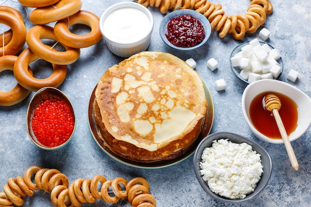 Shrovetide maslenitsa festival meal. russian pancake blini with raspberry jam, honey, fresh cream and red caviar, sugar cubes, cottage cheese on light Free Photo