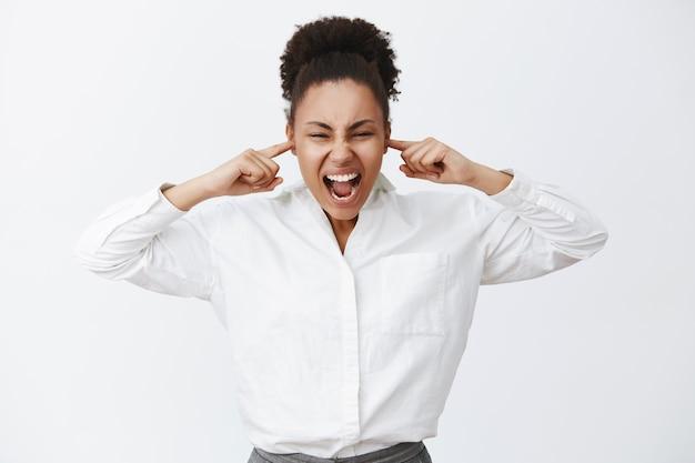 Zitti tutti. ritratto di donna di affari afro-americana femminile in difficoltà intensa in camicia bianca, gridando mentre chiude le orecchie con le dita, essendo incazzato e arrabbiato, in piedi in posizione rumorosa Foto Gratuite