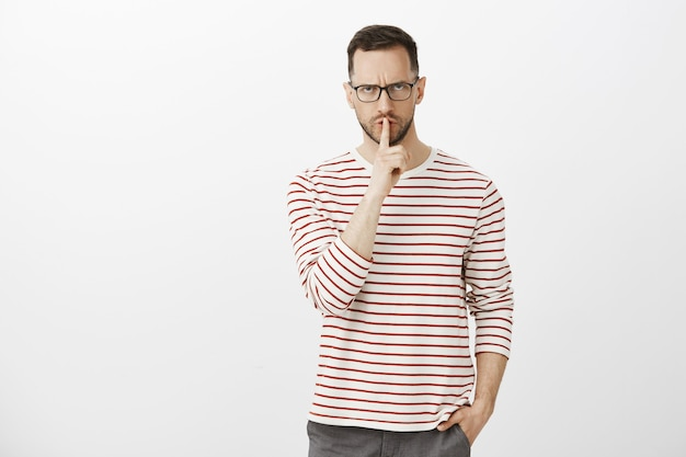 Shut up, shh. portrait of strict displeased male teacher in black glasses, frowning and looking from under forehead, making shush gesture with index finger over mouth, holding hand in pocket Free Photo
