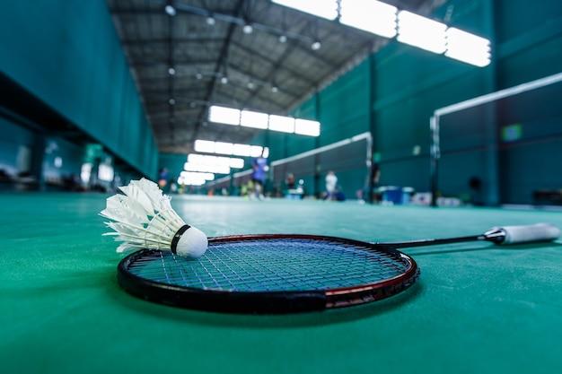 Shuttlecocks and badminton racket on green court Premium Photo