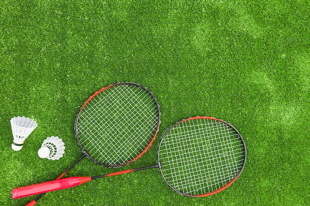 Shuttlecocks with red badminton on green turf backdrop Free Photo