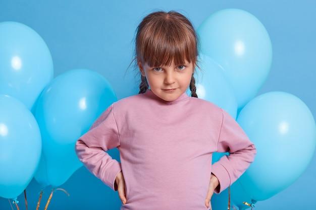 色の背景の上に分離された青い気球でポーズをとって恥ずかしがり屋の愛らしい小さな子供の女の子。額の下からカメラを見て、腰に手を保ち、バラのセーターを着ている美しい子供。 無料写真