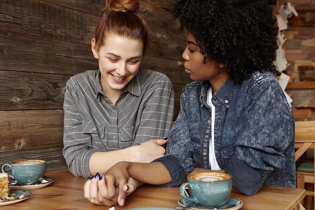 コーヒーショップに座ってうれしそうに笑って髪のお団子と恥ずかしがり屋の美しい赤毛の女性 無料写真