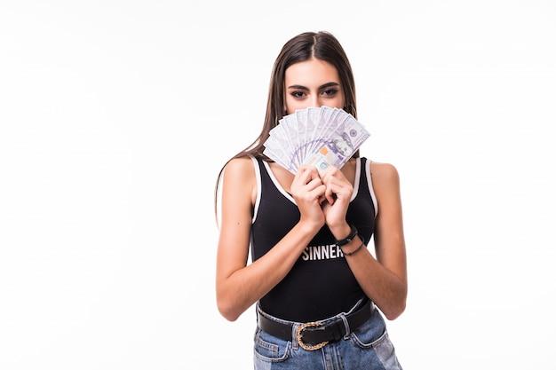 Застенчивая брюнетка в коротких синих джинсах держит веер долларовых купюр Бесплатные Фотографии