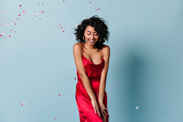 Застенчивая кудрявая женщина, стоящая под конфетти Бесплатные Фотографии