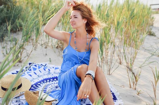 砂の上に座って、トレンディな青いドレスの太陽が降り注ぐビーチでポーズ完璧な日焼けした肌と内気な少女。風の強い髪。夕方の日差し。 無料写真