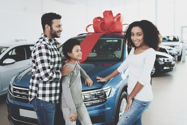 Shy woman choosed car touches hood of automobile. Premium Photo